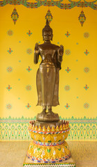 standing buddha statue with the yellow paint background