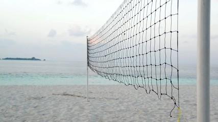 Torn beach volleyball net at tropical beach
