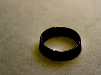 Old vintage metal thick ring on beige background