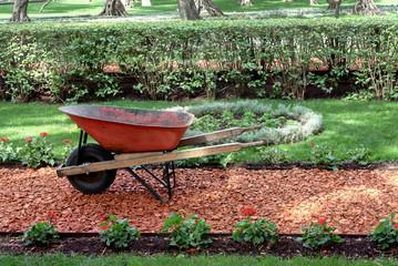 Garden work concept with wheelbarrow, soil and beautiful garden.