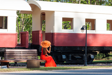 Young woman in red dress waiting train on the platform of