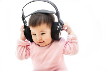 One snall happy baby girl listens music song with headphone