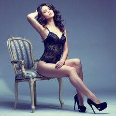 Beautiful young woman in sexy lingerie sitting in antique armcha
