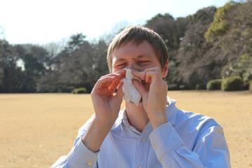 公園で鼻を擤む男性