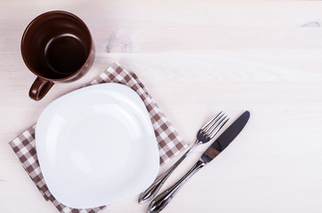 Fork with knife, blank plates, empty cup and napkin. On wooden t