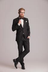 handsome young elegant man standing on studio background