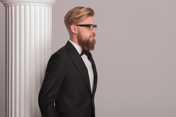 blonde business man posing near a white column