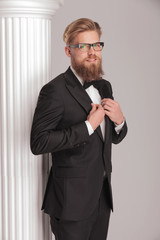 Elegant business man posing near a white column