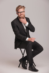 business man sitting on a stool while fixing his beard