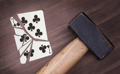 Hammer with a broken card, seven of clubs