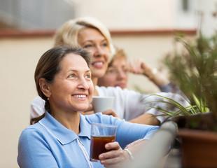 Three women drinking tea at balcony