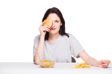 picture of woman with fruits and hamburger in front on white bac