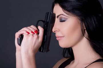close up portrait of young beautiful woman with gun over grey