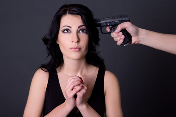 young beautiful woman hostage and male hand with gun over grey