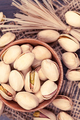 Pistachio super food mix in a wooden bowl with vintage toning