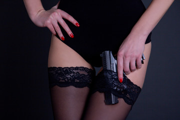 beautiful sexy woman in black lingerie with gun over grey