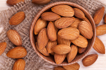 Almonds super food in a wooden dish on vintage textile backgroun