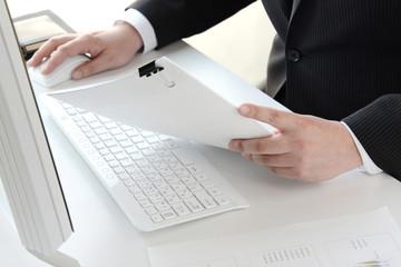 ビジネスイメージ―資料を見ながらパソコンを使うビジネスマン