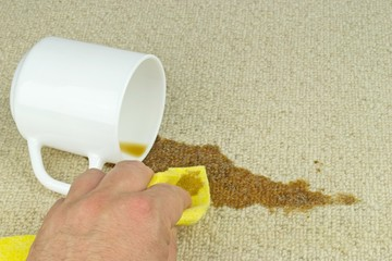 A hand with cloth cleaning a coffee stain from carpet