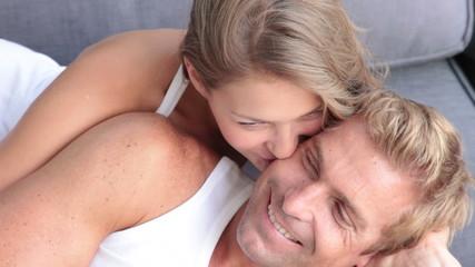 Young couple kissing on sofa