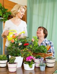 Two elderly women with flowerpots
