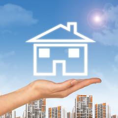 Female hand holding house icon