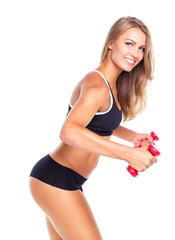 Young sports girl with dumbbells does exercises on a white