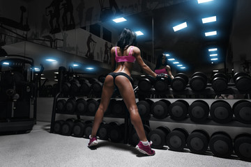 back view of sexy young brunette woman resting in the gym