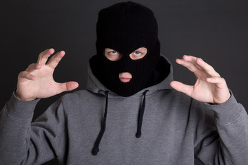 angry man criminal in black mask over grey