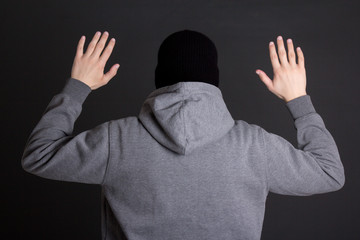 back view of man in black mask holding hands up over grey
