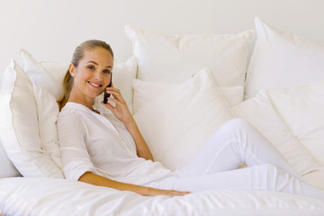 Young woman  phoning on sofa
