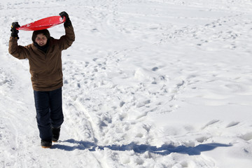 young boy walks with tobogganing on the head