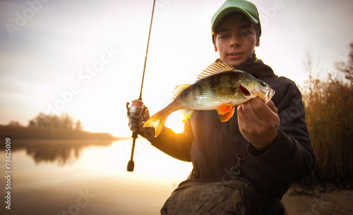 Happy angler with perch fishing trophy - 78625009