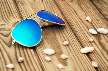 blue mirrored sunglasses and shells on the wooden background clo