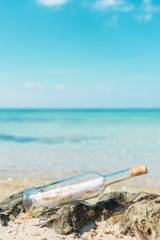 Bottle with message on the beach. Space for your text.
