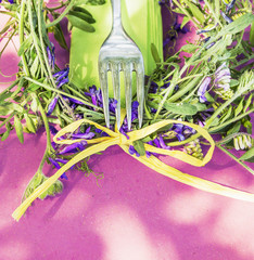pink table summer decoration with fork and vetch flowers and bow
