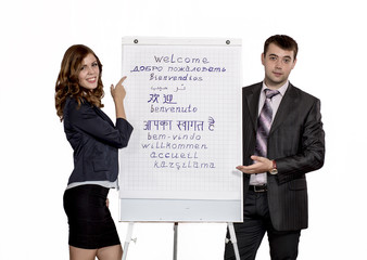 Business trainers welcome attendants pointing at flip chart