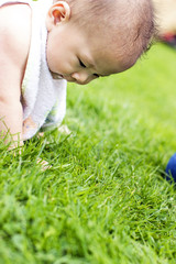 One happy baby sits on the grass in park