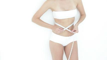 Woman taking waist measurement