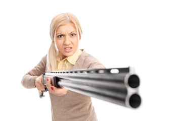 Angry girl pointing a rifle at the camera