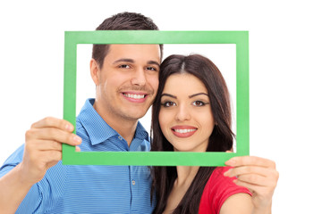 Couple posing behind a green picture frame