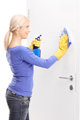 Female housekeeper cleaning a door