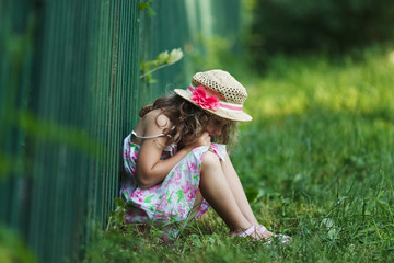 Sad little girl sitting on grass