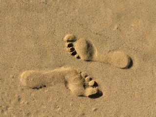 Gegenläufige Fußspuren im Sand
