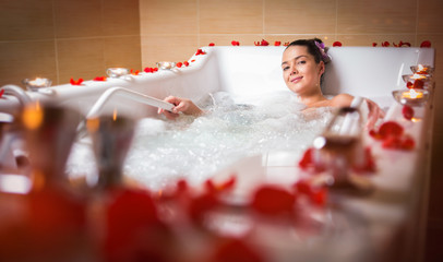 young beautiful brunette woman takes bubble bath