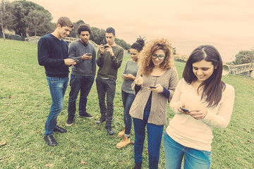 Multiethnic group of friends looking at their own smart phone