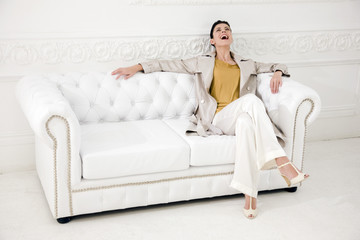 Woman laughing on a sofa