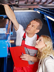 Mechanic with female customer in a garage