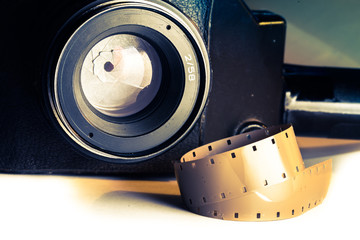 Film strips closeup with vintage movie cinema camera