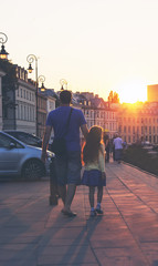 Father and daughter is walking in city at sunset. Toned